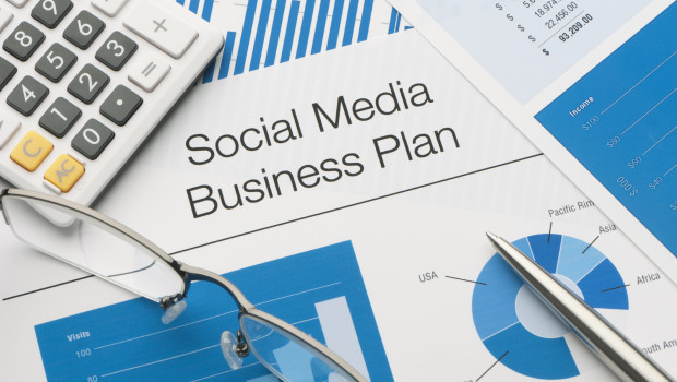 Close up of a social media business plan with pen and calculator