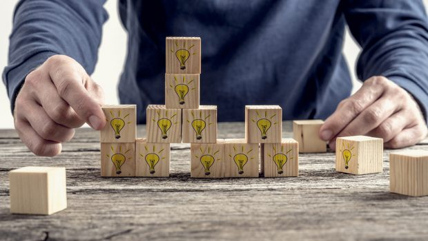 Front view of a man arranging wooden blocks with hand drawn yellow lightbulb in a random structure. Conceptual of research education and innovation.