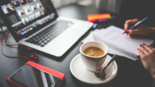 Coffee-filled Cup on Saucer Beside Macbook and Iphone on Desk