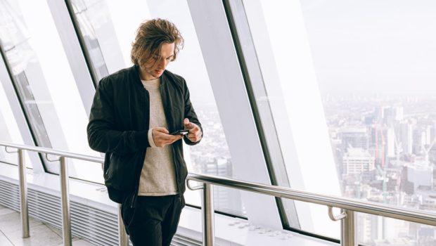 Man in Black Jacket Walking Beside Large Window