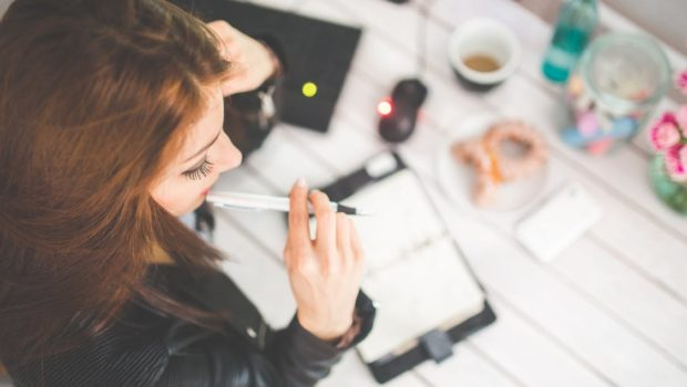Young woman thinking with pen while working / studying at her desk